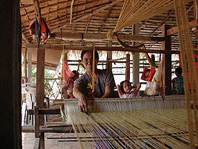 Panmai weaver at her loom, Thailand